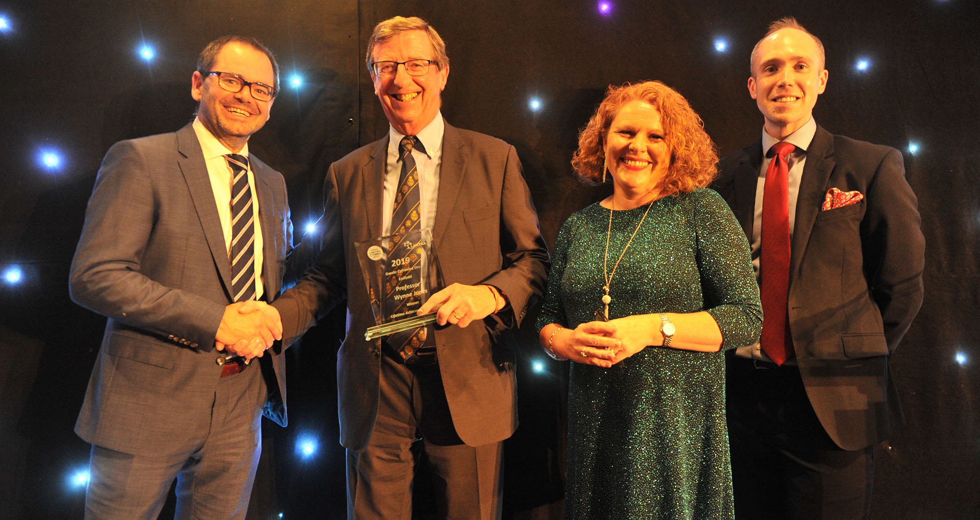 Professor Wynne Jones receiving his Lifetime Achievement Award from Mark Alexander (Welsh Government) and comperes Rachael Garside and Aled Jones